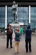 Fans take photographs of the Bobby Moore statue outside Wembley Stadium before the FA Vase match at Wembley Stadium, London<br /> Picture by David Horn/Focus Images Ltd +44 7545 970036<br /> 10/05/2014