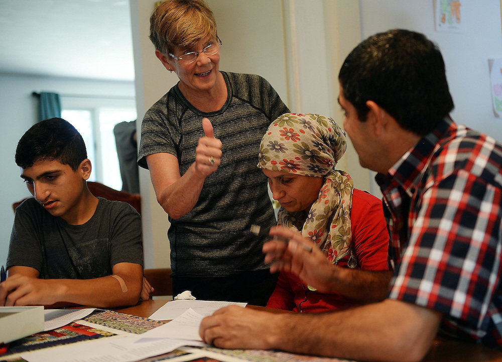 6/30/16 :: REGION :: LYNCH :: Sara Holdridge gives a thumbs-up to Hasan Mahmoud, right, as she works with him and his wife Fahima Jemmo, and their son Hanif, 15, left, on English language lessons Thursday, June 30, 2016. Hasan Mahmoud and Fahima Jemmo and their children Fidan, 17, Hanif, 15 and Fulla, 7, are refugees from the conflict in Syria and lived for three years in Turkey before finally receiving approval to come to the United States. (Sean D. Elliot/The Day)