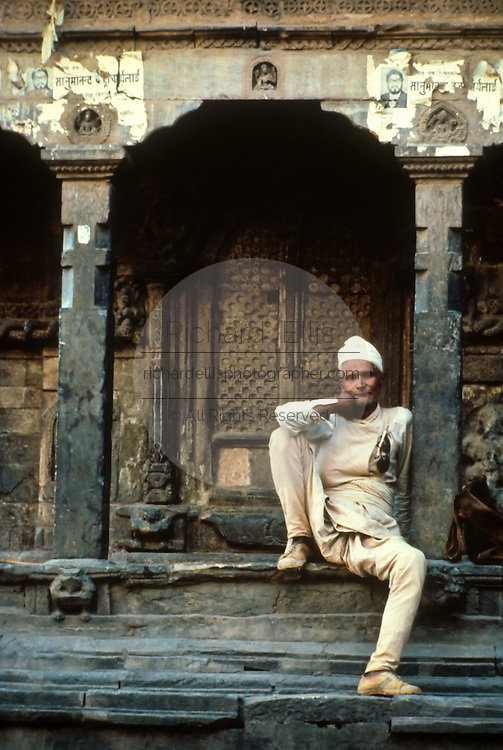 A Nepalese man in traditional clothing at a temple in Kathmandu Nepal