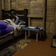 After a long day, Antonio Cruz Sanchez, 26, finally goes to sleep, as does Jango, his dog. Antonio gets up at 6:30 every morning to be able to spend a couple of hours tending to the SERES Embassy where he works and lives, before starting work as a facilitator for SERES, an NGO who provides leadership training for youth in many communities in Guatemala and El Salvador. San Juan Del Obispo, Guatemala, July 24, 2014