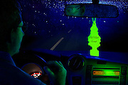 A glowing tree air freshener hangs from the mirror of a car being driven by a man at night.