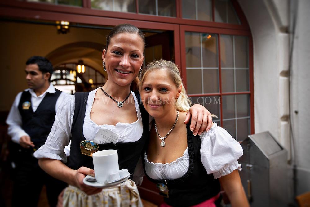 Women dressed in Dirndls outside the Hofbrauhaus, during Oktoberfest, Munich, Germany.