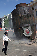 Policeman standing by the rocket in which the Litle Girl of the play landed, in Waterloo Place, central London, on Friday, May 5, 2006. The Sultan's Elephant show, for the first time in London is a magical, and unique in the world, theatrical show across the streets, performed by an international French company - Royal De Luxe - specialised in constructing and giving 'life' to enormous mechanical puppets. The Sultan's Elephant is the story of a Sultan dreaming of a little girl that travels through time. **ITALY OUT**
