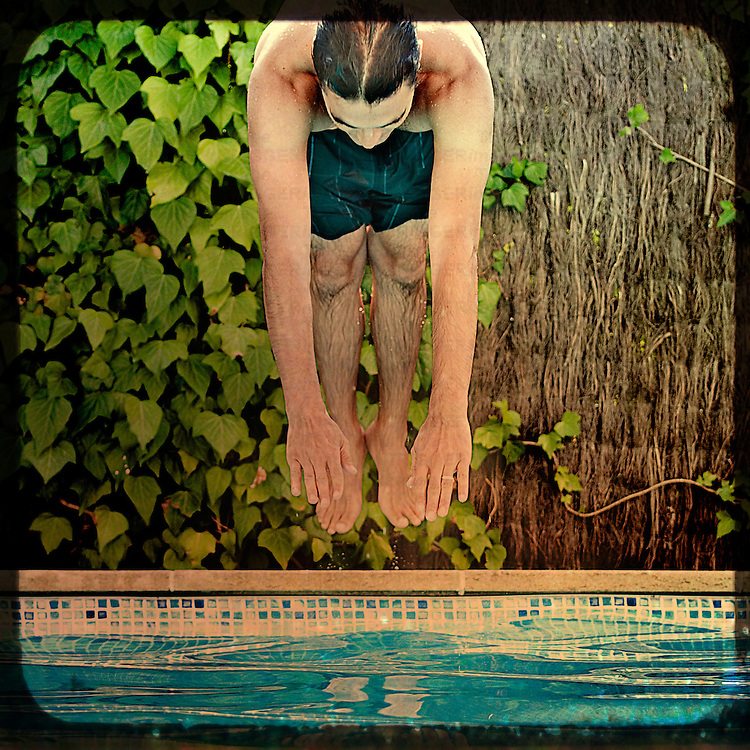 A young man diving into a swimming pool