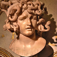 Medusa Bust by Gian Bernini at Capitoline Museums in Rome, Italy <br /> According to Greek mythology, Medusa was once a beautiful woman. But when she disavowed her chastity and married Poseidon, the god of the sea, she was turned into an ugly greenish gorgon. She had poisonous snakes for hair and turned to stone anyone who looked at her. This marble bust at the Hall of Geese (Sala delle Oche) at Palazzo dei Conservatori was sculpted by Gian Lorenzo Bernini in 1648. In current times, Medusa symbolizes female rage. She is also the logo for Versace, the high fashion company headquartered in Milan, Italy.