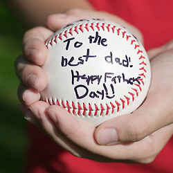 "Close up of child holding Inscribed baseball. ""To the best Dad! Happy Fathers Day!"""