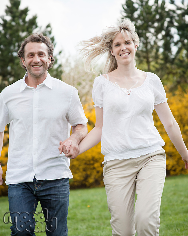 Close-up of Couple running through park holding hands