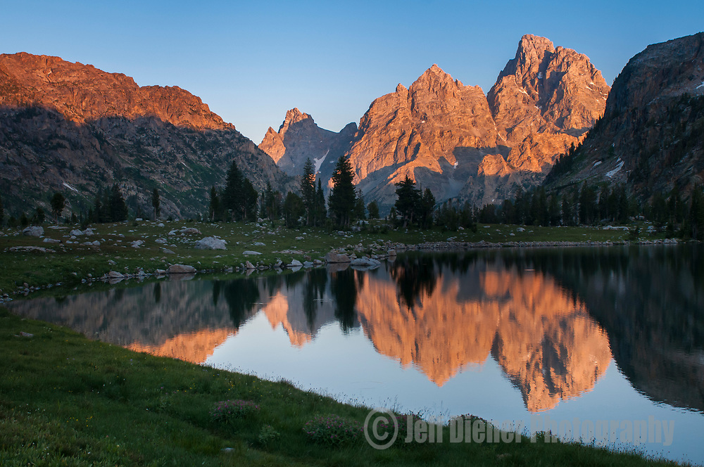 The high peaks of the Tetons are reflected in the waters of Lake Solitude at sunset  in Grand Teton National Park, Wyoming.