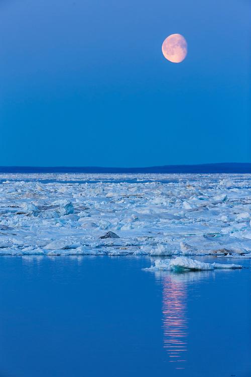 Canada, Nunavut, Territory, Moonrise above drifting sea ice along Frozen Strait in northern Hudson Bay near Arctic Circle
