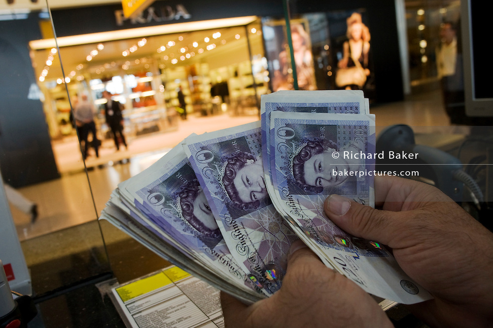 An assistant counts through Pounds Sterling notes at the Travelex bureau de change at Heathrow Airport's Terminal 5.