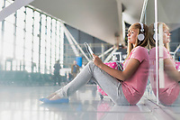 Portrait of young teenage girl sitting on the floor while watching movie on her digital tablet with headphones on in airport