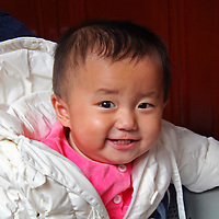 Asia, China, Shanghai. An adopted Chinese girl smiles from the lap of her new Spanish father.