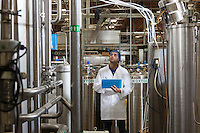 Factory worker inspecting bottling factory
