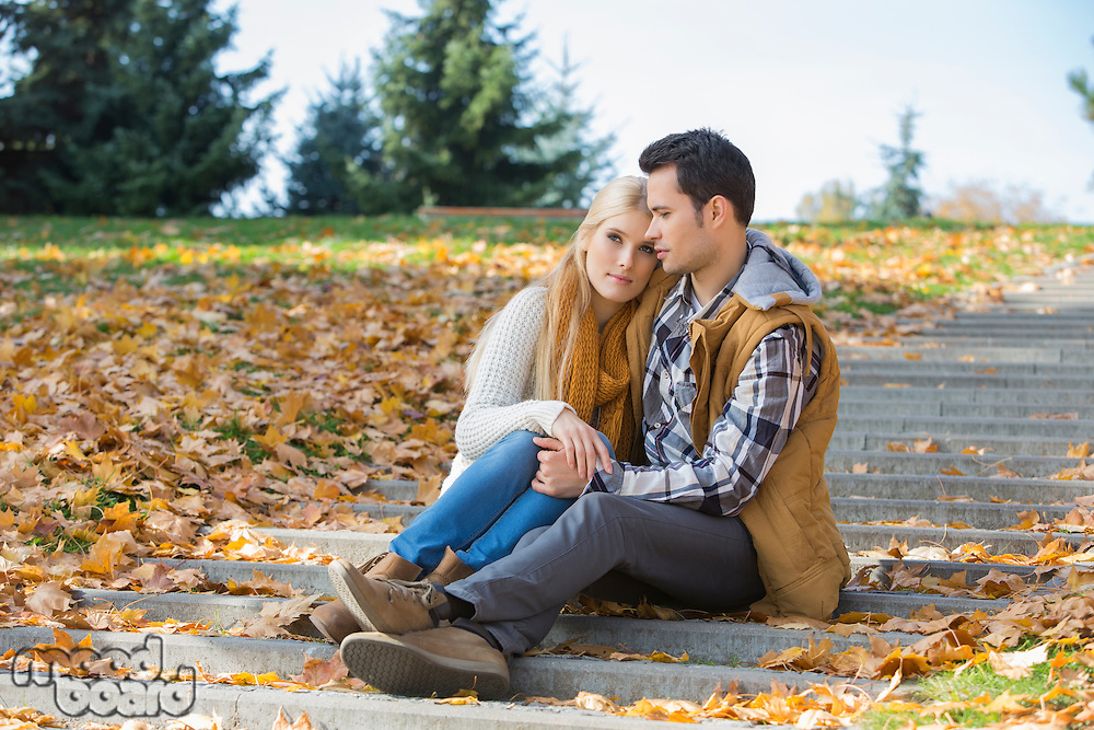 Loving couple sitting together on steps in park during autumn