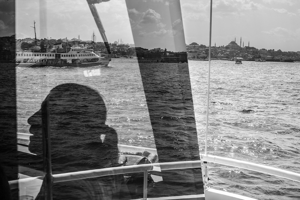The sillouette of one of the pilots of a boat that cruises the Bosphorus, seen through the glass with Istanbul landscape on the background.