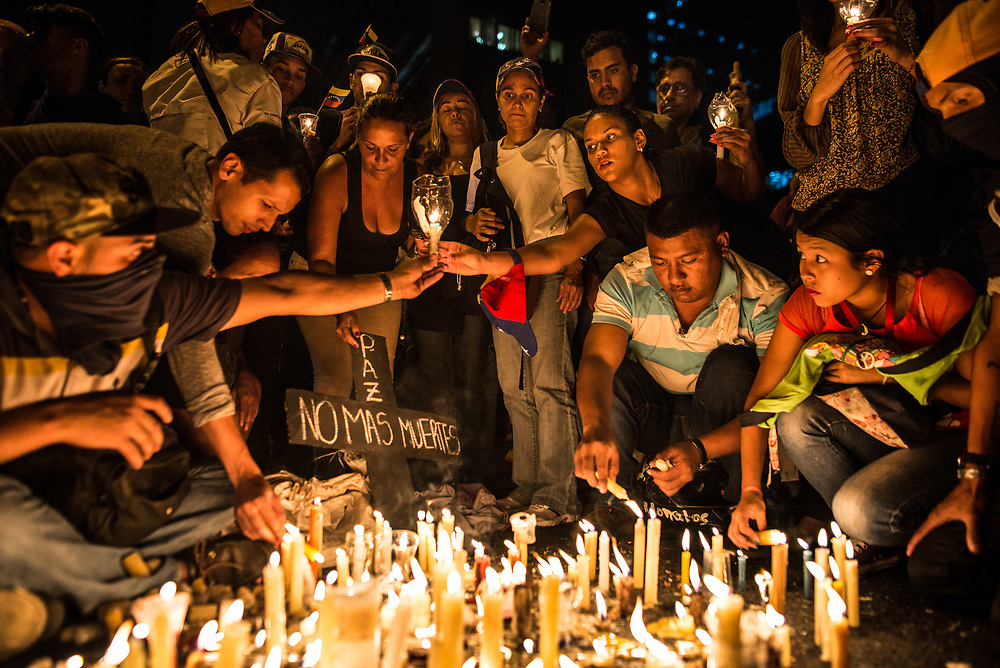 "CARACAS, VENEZUELA - MAY 17, 2017: People light candles during a vigil in memory of members of ""The Resistance"" killed by authorities during street protests. The streets of Caracas and other cities across Venezuela have been filled with tens of thousands of demonstrators for nearly 100 days of massive protests, held since April 1st. Protesters are enraged at the government for becoming an increasingly repressive, authoritarian regime that has delayed elections, used armed government loyalist to threaten dissidents, called for the Constitution to be re-written to favor them, jailed and tortured protesters and members of the political opposition, and whose corruption and failed economic policy has caused the current economic crisis that has led to widespread food and medicine shortages across the country.  Independent local media report nearly 100 people have been killed during protests and protest-related riots and looting.  The government currently only officially reports 75 deaths.  Over 2,000 people have been injured, and over 3,000 protesters have been detained by authorities.  PHOTO: Meridith Kohut"