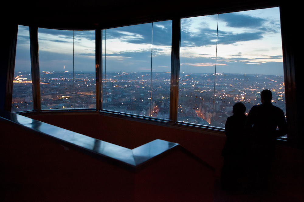 A couple is watching the evening cityscape of Prague from the Zizkov television tower located in Prague 3 - Zizkov.