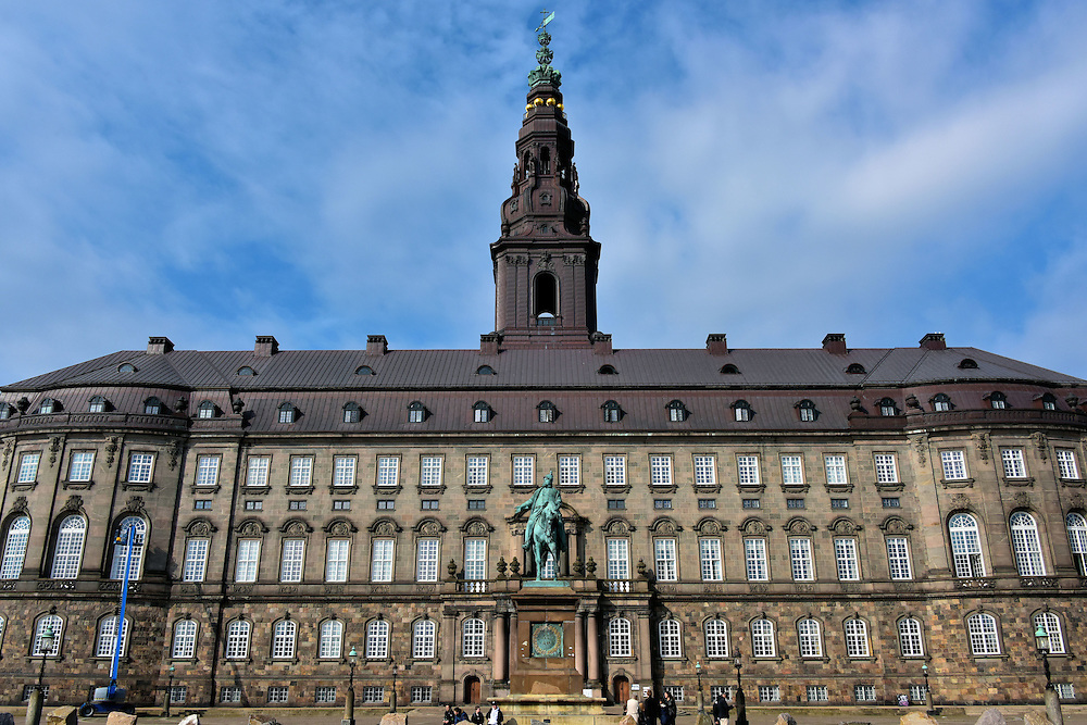 Christiansborg Palace in Copenhagen, Denmark <br /> There have been two castles and three palaces that have stood here on an island appropriately called Slotsholmen which means The Castle Islet.  The first was built by Bishop Absalon in 1167. The current Christiansborg Palace was built in 1928.  It houses all three executive branches of the Danish government including the offices of the Supreme Court and the Prime Minister.  It is also used by the royal monarchs on special occasions.  The spire reaches a height of almost 350 feet.