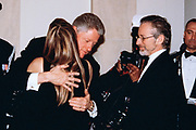 U.S. President Bill Clinton, center, embraces actress Kate Capshaw as her husband film director Steven Spielberg, right, looks on in the receiving line during the State Dinner at the White House February 5, 1998 in Washington, DC.