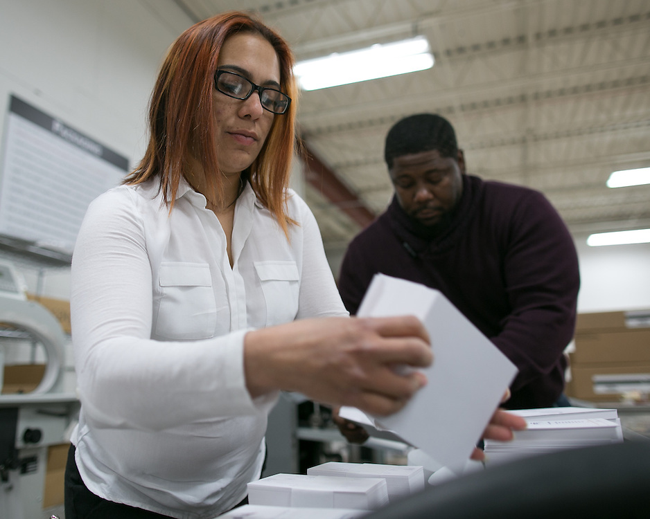 Zara Martinez and Jason Ellis pack printed materials at Phoenix Graphics in Rochester on Thursday, April 9, 2015.