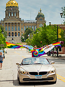 "28 JUNE 2020 - DES MOINES, IOWA:  A woman with American and Mexican versions of the Pride Flag participates in the Capitol City Pride Parade in Des Moines. The State Capitol is in the background. Most of the Pride Month events in Des Moines were cancelled this year because of the COVID-19 pandemic, but members of the Des Moines LGBTQI community, and Capitol City Pride, the organization that coordinates Pride Month events, organized a community ""parade"" of people driving through the East Village of Des Moines displaying gay pride banners and flags. About 75 cars participated in the parade.     PHOTO BY JACK KURTZ"