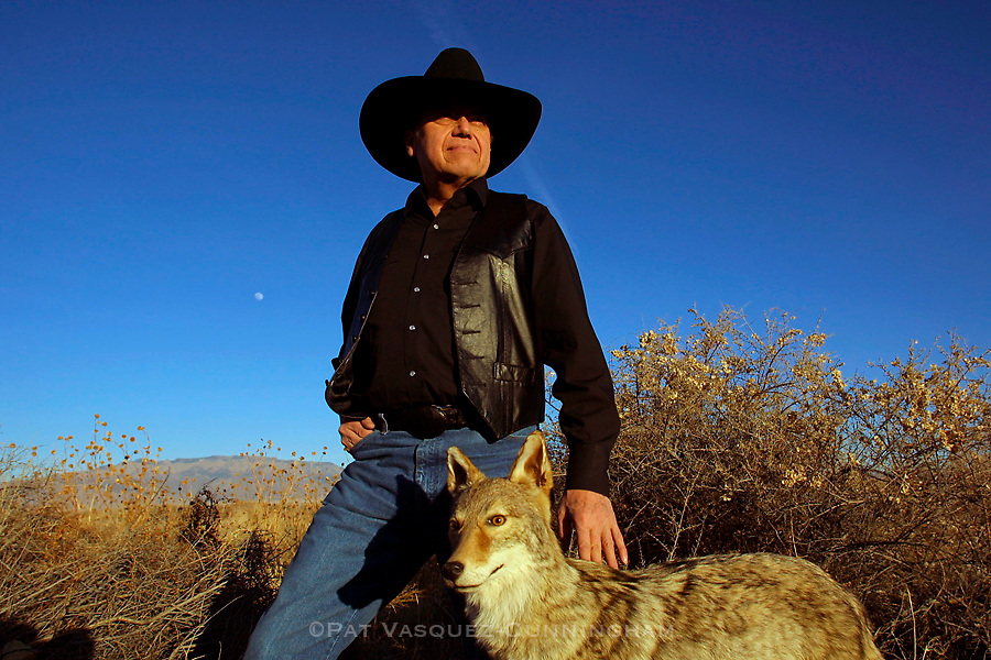 Artist John Nieto stands for a portrait next to a stuffed coyote he sometimes incorporates in his paintings, photographed near his Albuquerque, N.M. home Saturday Jan. 26, 2002.  (AP Photo/Pat Vasquez-Cunningham)