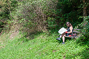 Female cyclist sits on a forest bench to study the cycle path maps. Model Release Available