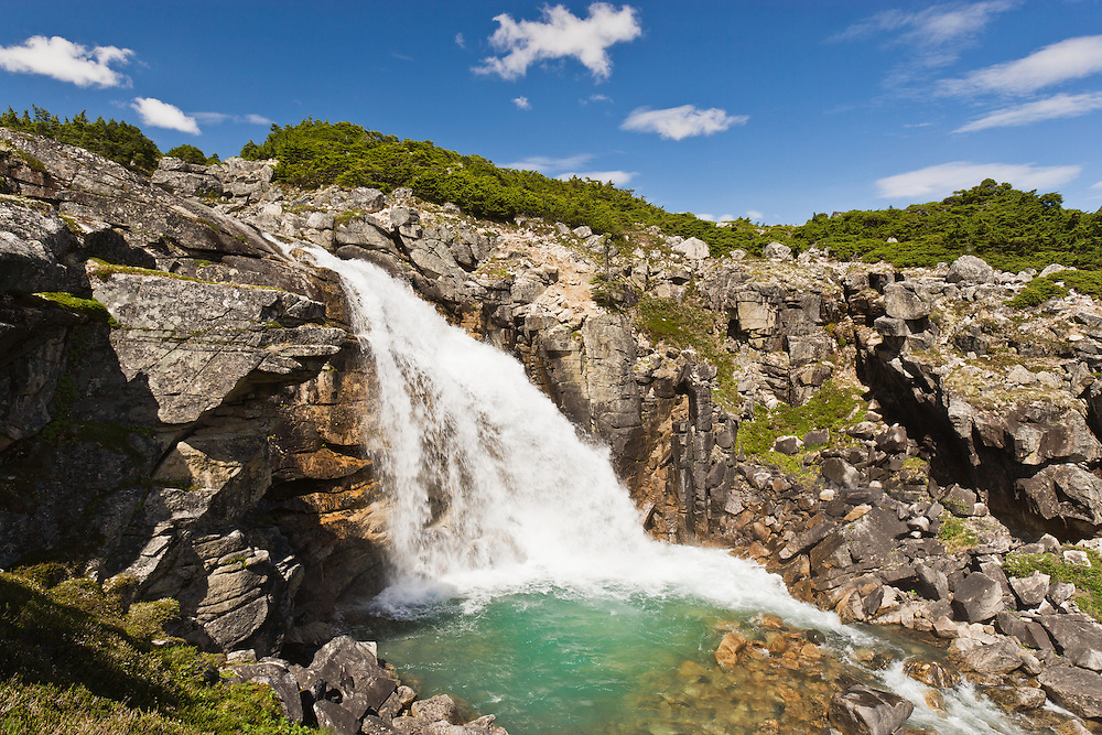Landscape view of unnamed waterfalls near border with Canada outside of Skagway in Southeast Alaska. Summer. Afternoon.