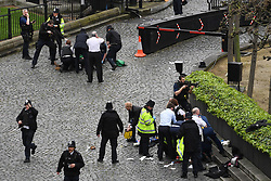 PABEST A policeman points a gun at a man on the floor at the top of the frame as emergency services attend the scene outside the Palace of Westminster, London, after a policeman was stabbed and his apparent attacker shot by officers in a major security incident at the Houses of Parliament.