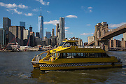 A yellow New York Water Taxi boat sails along the East River, just passing under the Brooklyn Bridge, with Lower Manhattan on the other side of the river.  Photographed across the East River from Brooklyn, New York City, New York, United States of America.(photo by Andrew Aitchison / In pictures via Getty Images)