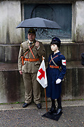 A Japanese man,  in Imperial Army uniform, holds an umbrella over a model of a child wearing a nurses uniform from the Pacific War as Yasukuni shrine marks the 72nd anniversary of the end of the Pacific War. Yasukuni Shrine, Kudanshita, Tokyo Japan. Tuesday August 15th 2017. Nominally a event to honour Japan's war dead and call for continued peace, this annual gathering  at Tokyo's controversial Yasukuni  Shine also allows many Japanese nationalists to display their nostalgia for their Imperial past.Rightwing paramilitary groups, Imperial cos-players, politicians and many ordinary citizens come together at the shrine to march and wave flags. The day goes almost unreported in the mainstream Japanese media.