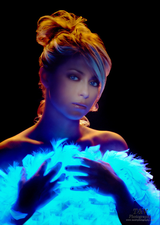 Pretty woman wearing a glowing feather boa against a dark background.Black light
