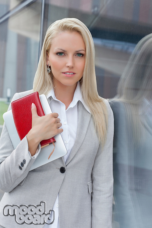 Beautiful businesswoman holding organizer and digital tablet while looking away by glass wall