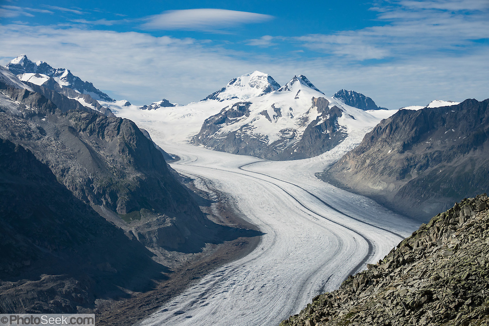 See the vast Aletsch Glacier from atop the Eggishorn in Valais canton of Switzerland, the Alps, Europe. From Fiesch, ascend via cable car first to see stunning views from the Eggishorn (2926 m), then return to the mid station of Fiesheralp, from where you can hike a spectacular ridge above Aletsch Glacier via Hohbalm, Moosfluh, Hohfluh, Riderfurke, and Riederalp. Grosser Aletschgletscher is the largest glacier in the Alps (23 km or 14 miles long in 2014). The Swiss Alps Jungfrau-Aletsch region is honored as a UNESCO World Heritage Site.