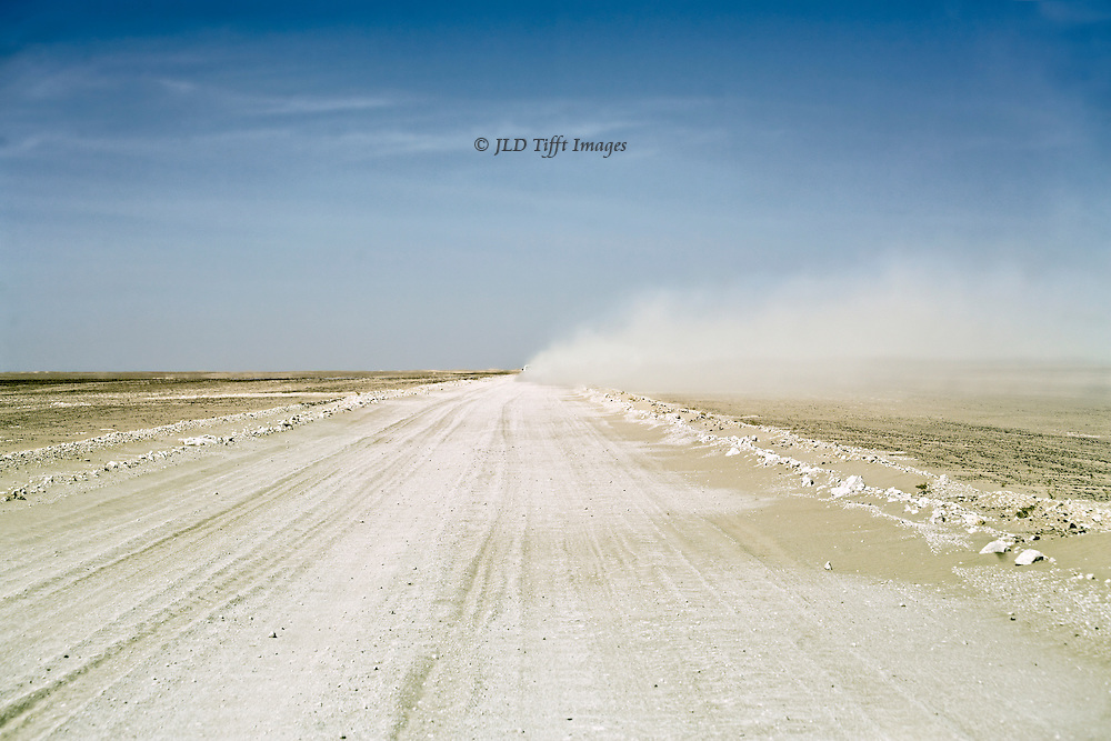 Road across the hard flat desert of southern Oman.  View along the road toward a cloud of dust raised by a speeding jeep as it disappears in the distance.  Flat blue sky with wispy clouds above.