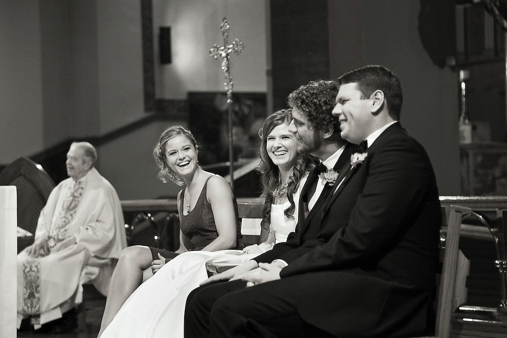 B&W photo of bride and groom sharing a laugh with their best man and maid of honor during their church wedding ceremony.