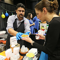 Fidel Cubillo, owner of D'Casa in Tupelo, serves a bowl of chips with ground beef, sauce and cheese to Leah Patterson, of Tupelo, during The Taste of Tupelo Thursday night at the BancorpSouth Arena in Tupelo.