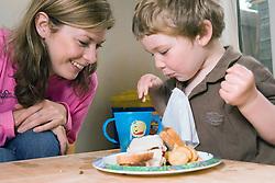 Nanny feeding little boy,