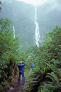 Hikers admire magnificent Sutherland Falls which plunges 1904 feet or 580 meters in three tiers, on the Milford Track, South Island, New Zealand. In 1990, UNESCO honored Te Wahipounamu – South West New Zealand as a World Heritage Area.