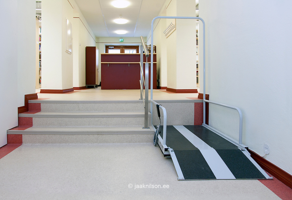 Corridor with set of three steps and wheelchair lift or ramp. Disabled access