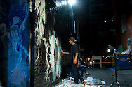 Joseph Durbin works on his mural late in the evening of August 6, 2016 during the Freak Alley Gallery sixth annual mural event in downtown Boise, Idaho.<br /> <br /> Joseph didn't realize that he was going to have such a big piece to do. Painting for him is a great outlet. Although he works hard in a manual labor job, putting in the extra work to do something like this was a positive for him.<br /> <br /> He thinks that colorful makes you happy and he has always enjoyed seeing swirls, like Starry Night, and loves the feeling that it gives. He incorporated these into his mural as his way to express a positive message in his work. <br /> <br /> Freak Alley Gallery's week long event provided an &quot;art-in-motion&quot; experience as it welcomed the public to watch artists work on their murals.