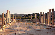 Main street, connecting the inner harbour to the agora in front of the bouleuterion, Hellenistic period, Patara, Antalya, Turkey. This is a Cardo (North-South street) which intersects with the Decumanus (East-West street). It is 12.6m wide and has a colonnade of granite Ionic columns on its East side and one of marble columns on the West, behind which are shops of varying sizes. This colonnaded wide avenue was completely flooded after the earthquakes in the region, and so far, it has been unearthed over 100m. The lack of wheel marks suggests that it functioned as a pedestrian street. There is a sewer system running underneath the street. Patara was a maritime Greek and Roman city on the South West Mediterranean coast of Lycia near modern-day Gelemis. It was said to be founded by Patarus, son of Apollo, and was famous for its temple and oracle of Apollo. It was a leading city of the Lycian League. Picture by Manuel Cohen