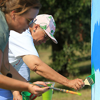 Nettie Davis, Tupelo Ward 4 Councilwoman, and Belle Naugher, Director of the GumTree Museum of Art, work together on painting a mural on the storm shelter on Front Street in Tupelo Wednesday. The project, started by Davis, is to beautify the shelter in conjunction with Keep Tupelo Beautiful.