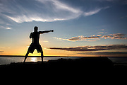 A man is silhouetted training on a jetty at sunset.