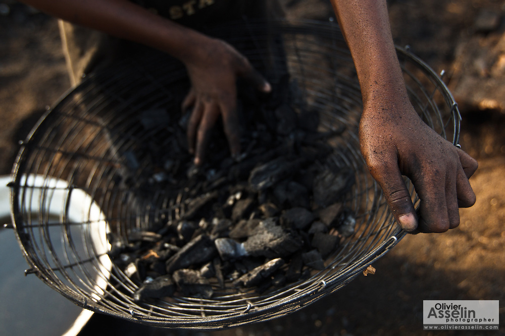 A girl sorts pieces of charcoal at a wood charcoal production site on the outskirts of San Pedro, Bas-Sassandra region, Côte d'Ivoire on Sunday March 4, 2012. Men, women and children - who don't go to school - work here seven days a week.