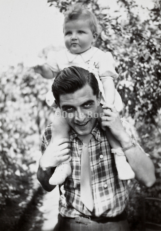 father caring his little girl on his shoulders France 1950s