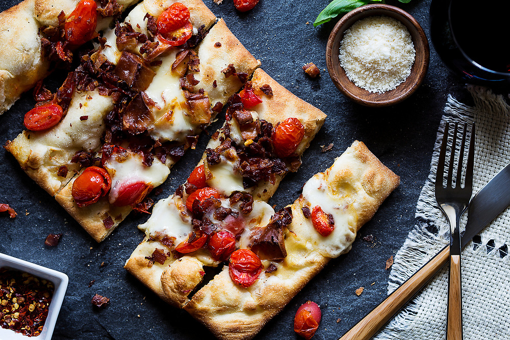 Top-down shot of flatbread pizza with tomatoes and prosciutto.