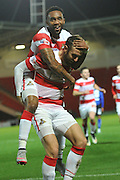 Cedric Evina  of Doncaster Rovers  climbs on Andy Williams of Doncaster Rovers to celebrate Andy Williams of Doncaster Rovers scoring to go 2-0 up during the Sky Bet League 1 match between Doncaster Rovers and Chesterfield at the Keepmoat Stadium, Doncaster, England on 24 November 2015. Photo by Ian Lyall.