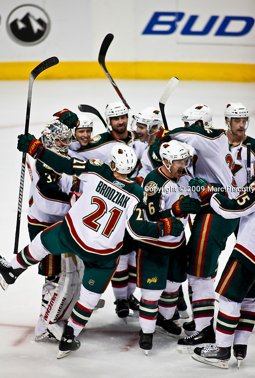 SHOT 11/28/09 10:43:32 PM - The Minnesota Wild's Kyle Brodziak (#21) celebrates with teammates after an overtime shootout win against the Colorado Avalanche in their regular season NHL game at the Pepsi Center in Denver, Co. The Minnesota Wild won the game 3-2 in an overtime shootout. (Photo by Marc Piscotty / © 2009)