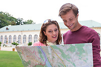Young tourist couple with map against building